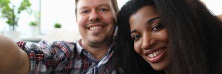 Diverse millennial couple people make face selfie photo against home background portrait. Happy adult family marriage concept