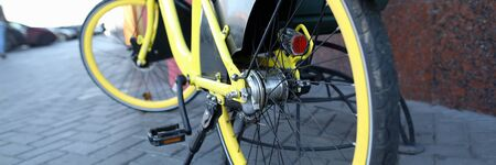 Close-up view of bike parked and secure with locking device on street. Trendy modern yellow bicycle. Healthy lifestyle and environmental form of transport concept
