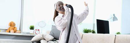 Woman sing song in vacuum cleaner against modern home background. Happy clean concept Zdjęcie Seryjne