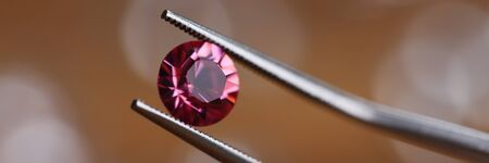 Jeweler in workshop holds pink stone in tweezers clamp closeup. Gemstone processing concept