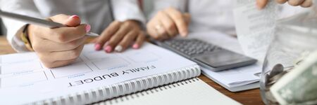 Focus on married couple plan calendar. Husband and wife coping with financial problems. Man with bills calculating expenses. Woman writing down info on notebook. Spouse controlling money