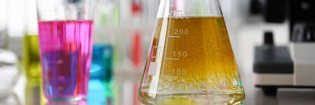 Close-up of test-tubes with colorful chemical reagent. Laboratory glassware and expertise. Microscope on background. Chemistry and investigation concept Stock Photo