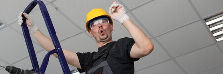 Portrait of man standing on ladder showing signs of new approach. Person with screwdriver or drill finding ways of apartment improvement. Handyman wearing helmet and glasses Reklamní fotografie