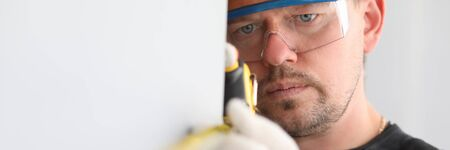 Portrait of man with roulette looking at precise number on ruler. Handyman with helmet and glasses checking straightness of construction. Builder with gloves Reklamní fotografie