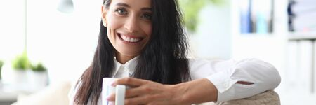 Portrait of successful cheerful businesswoman having tea time at office. Positive smiling businesslady in white stylish blouse looking at camera with gladness. Business concept