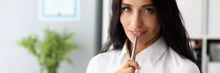 Portrait of sensual businesslady working at office. Attractive woman holding pen and notepad. Charming female posing and looking at camera with tenderness. Business concept