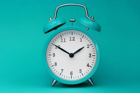 Modern alarm clock turquoise closeup object. Time online system concept