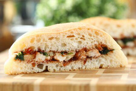 Cut chiken sandwich with ketchup against kitchen closeup background. Reklamní fotografie