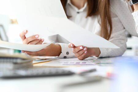 Focus on tender female hands holding important business documents with significant charts and graphs used for special corporation analysis. Accounting office concept. Blurred background