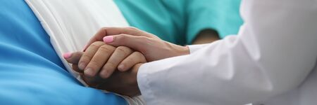 Female doctor hands hold male arm in medical hospital closeup. Medicine work drama concept Banque d'images