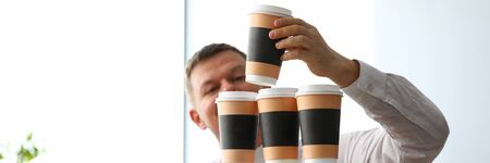 Stupid office clerk making huge tower out of paper cups close-up