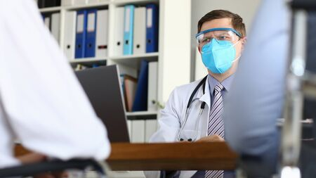 Male doctor suspiciously looks at patient suspects severe stage of chinese coronavirus. Medical education concept