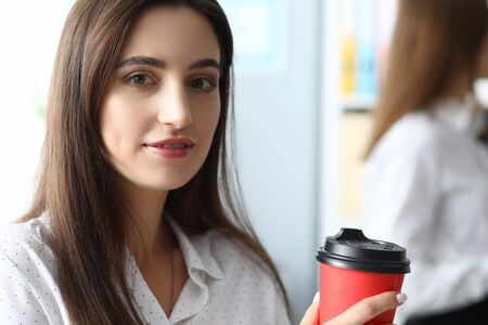Portrait of smart businesswoman in white blouse looking at camera with gladness and standing indoors with red paper cup of coffee. Witty woman in modern office 版權商用圖片