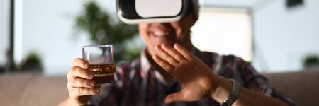 Man sit at sofa hold glass in hand and using vr gogles. Online party drinking companion concept