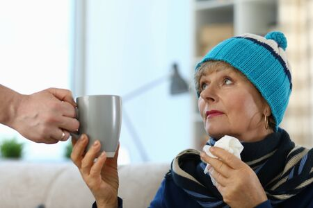 Cold elderly lady in knitted hat takes cup tea. Side effects drugs. Cold medicine for elderly. Parents are difficult to tolerate, suffer from complications. Weak immune system in old age