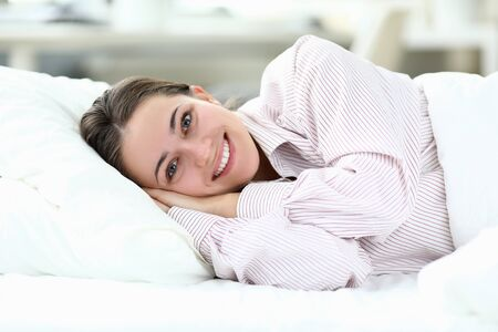 Happy girl in pajamas lies on bed and smiles. Help your body make transition to wakefulness more enjoyable. Change your lifestyle. Comfortable stay at hotel. Tune in for early awakening Stock Photo