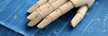 Close-up of wooden prosthesis hand lying on construction project. Blueprint with sketches and calculations. People with disabilities and business concept