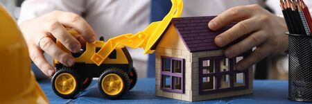 Close-up of male hands with yellow toy excavator. Builder driving backhoe loader on blueprint. Businessman in white shirt with tie. Construction and business concept