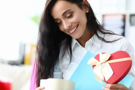 Happy girl looks at gift form heart from package. Use services personal shoppers. Consciously approach process buying new clothes. Make sets with fashionable things already in wardrobe