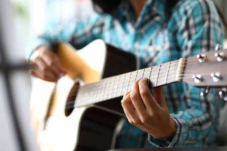 Skillful musician fingers on guitar fretboard. Woman plays chords on acoustic guitar, in her other hand convenient pick. Student performs exercises on instrument to improve abilities 版權商用圖片