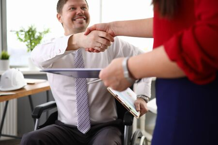 Close-up view of co-workers shaking hands and smiling to each other. Man in disabled carriage. Working process at company office. Employee holding folder with papers. Business concept