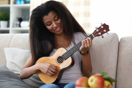 Portrait of lovely smiling afro-american woman playing on ukulele. Young female enjoying performing melody on musical instrument. Music and entertainment concept