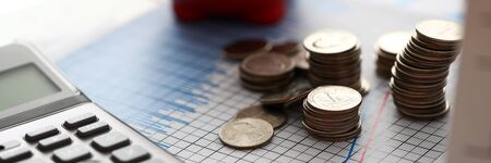 Close-up of golden metallic coins and pen lying on important charts and graphs used for profitable business corporation investment investigation and forwarding cooperative movements. Reports sale concept