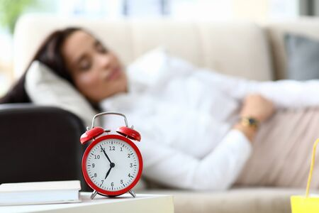 Girl is tired and lies on table an alarm clock. Woman is tired spending lot time shopping. Female shopping escort. On table is an alarm clock, woman is sleeping in clothes on couch