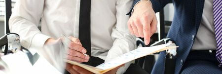 Male hand in suit and tie showing something important in tax interview document closeup Foto de archivo