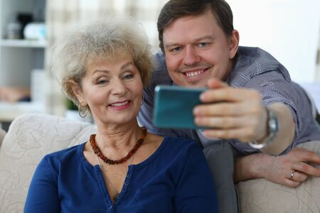 Portrait of cheerful mother and son taking selfie to remember. Smiling elderly woman posing for picture on sofa at home. Family relationship and spare time concept