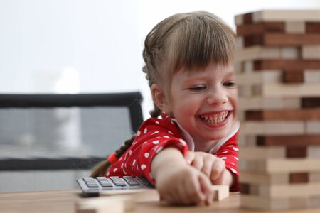 Girl child sit table and laughs while playing game. Development fine motor skills in children. Girl knows how to think and reason logically. Player kid from bars players build tower