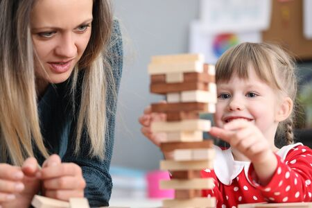 Mom and daughter stack blocks on top each other. Child is taught to choose right subject. Girl movements are awkward, inept and inharmonious. Children and adults communicate, play Stock Photo