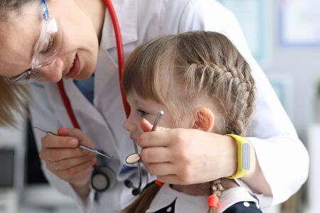Pediatric dentist examines teeth little girl. Examination oral cavity in children at various age periods. Identification pathological conditions teeth in girl. Diseases development in children