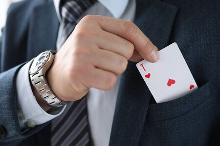 Man suit takes an ace card from his jacket pocket. One-sided advantage and benefit. Technique or manipulation trick. Demonstration bait. Manual control with levers, manipulator mechanisms