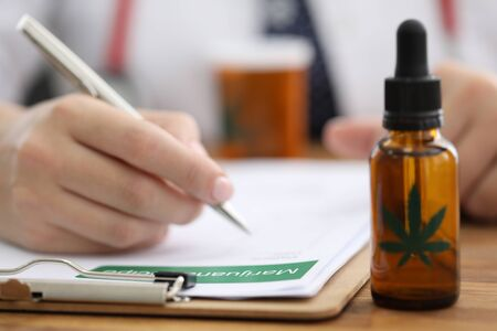 Closeup doctors hand writing prescription for hemp. Doctors prescribe cannabis for sleep disturbance. Hemp is part medication recommended for muscle spasms and epilepsy. Brain functioning 스톡 콘텐츠