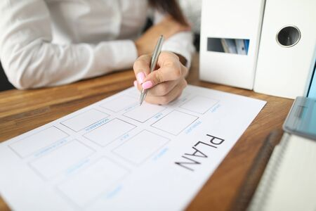 Woman draws up paper financial payment boards. Account grouping and cash flow analysis. Multilevel structure categories and projects. Consolidate finances balance for reporting period Imagens