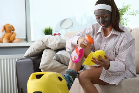 Girl with cosmetic mask on her face does cleaning. In everyday conditions, use conventional vacuum cleaner for cleaning. Effectively organize spring cleaning. Polished wooden parts furniture