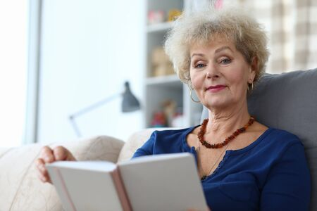 Elderly woman self-isolation reading book at home. Coronavirus pandemic conditions. Effective way to protect yourself from home quarantine infection. Do not leave home or receive visitors