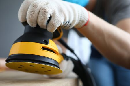 Close-up of persons hands polishing ground with grinding machine. Bright yellow sander instrument and craftsman on construction site. Protective gloves for work. Renovation concept 版權商用圖片