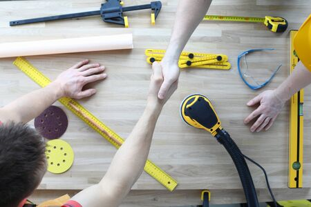 Top view of worker welcome each other and shake hands. Sander machine level replacement discs and ruler on wooden table. Carpenter and construction site concept