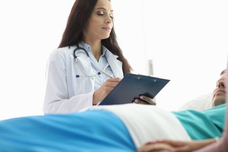 Female doctor stands over man lying hospital bed. Nurse records patients indicators. Department Anesthesiology and Intensive Care. Correction simultaneous appointments narrow-profile specialists