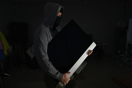 Portrait of man wearing grey hoodie and black mask. Male thief standing in dark room and holding expensive televisor from popular company. Stealth robbery concept