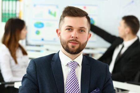 Jeune greffier souriant en costume-cravate à la tête de l'appareil photo
