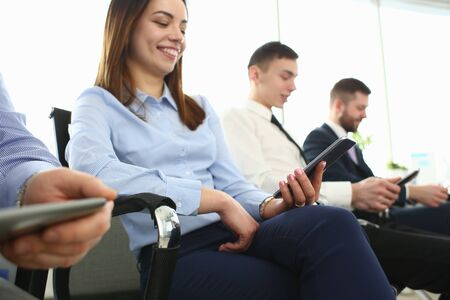 Bunch of people holding in hands electronic gadgets while sitting in line closeup