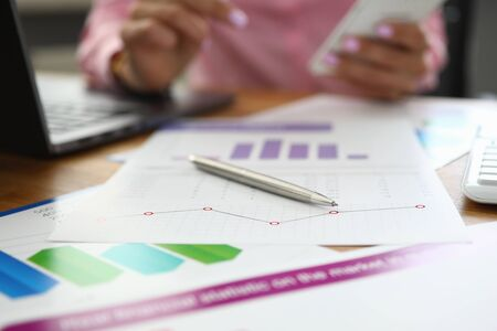 Close-up of business papers with diagrams and charts. Documents laying on desktop in office. Female secretary at working place. Laptop on desk. Economy and finance concept Imagens