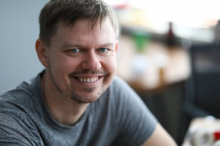 Close-up of smiling middle-aged man looking in camera. Cheerful attractive person dressed in grey shirt. Copy space in right side. Modeling and happiness concept