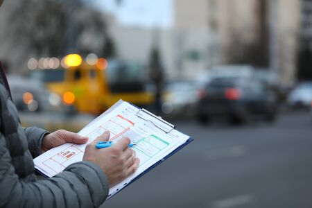 Close-up of male insurance agent filling report claim form on clipboard. Copy space in right side. Automobile crash. Process after car accident and traffic concept