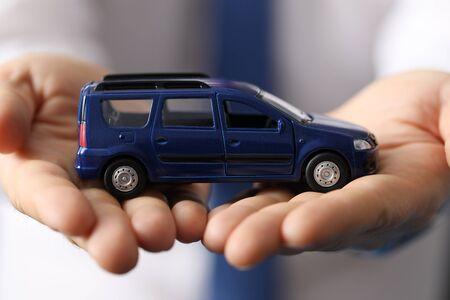 Closeup, man in shirt holds blue toy minivan car. Favorable car insurance. Inspection and diagnostics transport vehicles. International passenger transportation. Car sale from passenger compartment
