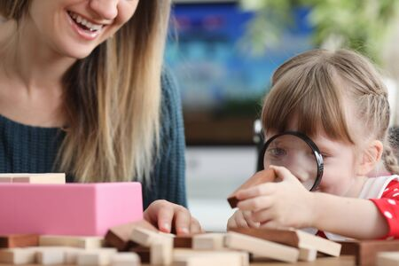 Daughter looks through magnifier at wooden bar. Girl learns to think strategically. Popular game among children and adults. Board game for development intelligence. Assemble tower, pull blocks out it