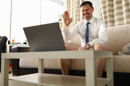 Man without trousers sits in front laptop at home. Organize remote team and set up to work outside office. Man holds video conference call with employees from home. Corporate chat for communication